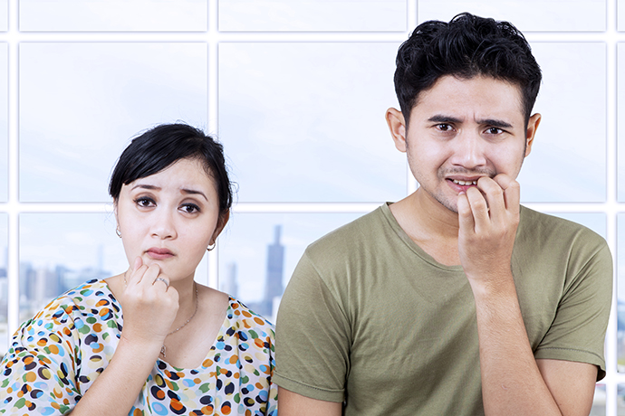Afraid couple biting nails in the apartment